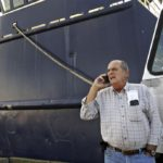 Carlos Rafael on the phone in front of a boat Photo credit: Peter Pereira/Standard-Times File/SCMG