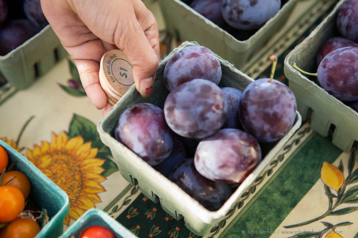 close up of hand holding pint of plums and wooden dollar coins at farmers market, credit: John Benford