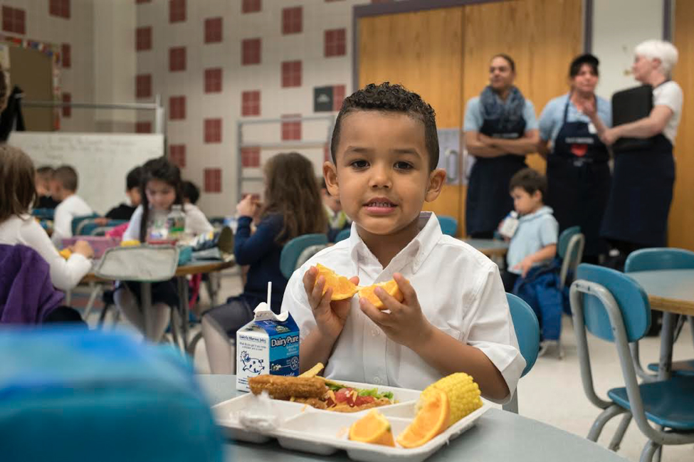 BPS student with lunch in cafeteria