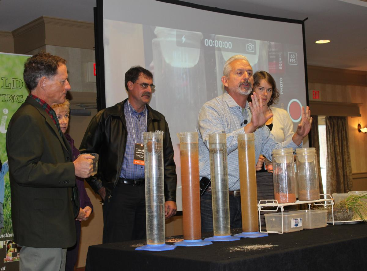 Ray Archuleta, Conservation Agronomist at the USDA Natural Resources and Conservation Service, demonstrates a soil stability test with Vermont farm and food industry leaders at the 2015 Farm to Plate Annual Gathering