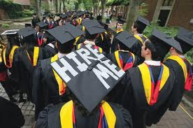 "graduates, one with ""hire me"" on cap"